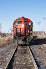 Head On View Of Red Locomotive On Tracks In City