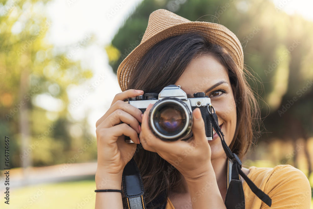 Fototapety, obrazy: Smiling young woman using a camera to take photo.