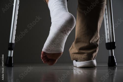 足を怪我した男、松葉杖 Fotobehang