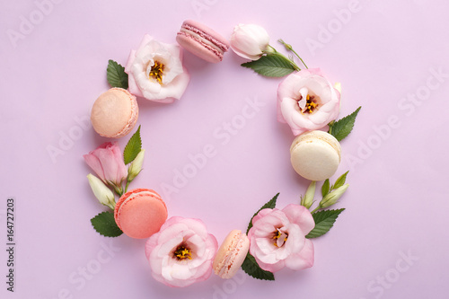 Macarons and flowers wreath on a purple background. Colorful french dessert with fresh flowers. Top view
