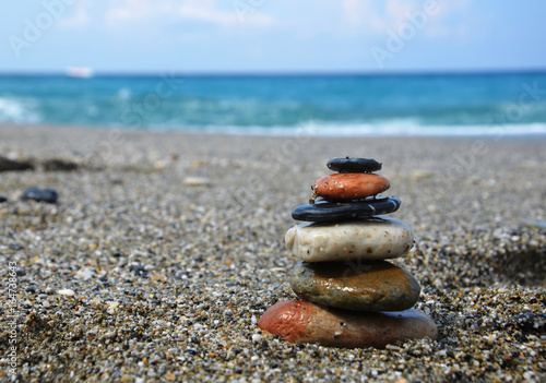 Foto op Plexiglas Stenen in het Zand Relaxing in the summer concept. Stones stacked on the beach on sea background