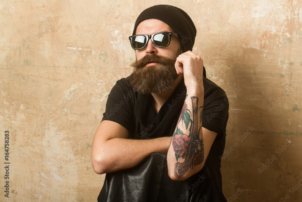 Fototapeta Hipster in leather jacket and hat with glasses.