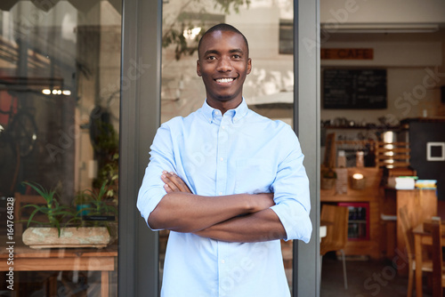 Fotografía  Smiling African entrepreneur standing outside of his trendy cafe