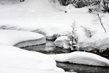 Narrow Tortuous River Or Stream Flows Between Banks Covered With Lots Of Snow In A Forest . Overcast Cloudy Day With Heavy Snowfalls