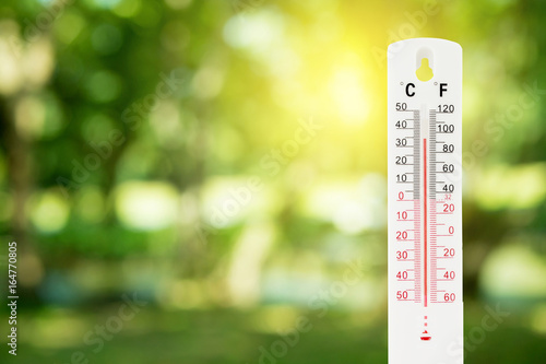 Fototapeta thermometer on a green nature background and temperature measuring, environment concept