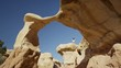 Wide panning low angle shot of man walking on arch rock formation / Escalante, Utah, United States