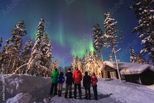 Poster Scandinavië Beautiful picture of massive multicoloured green vibrant Aurora Borealis, Aurora Polaris, also know as Northern Lights in the night sky over winter Lapland, Norway, Scandinavia
