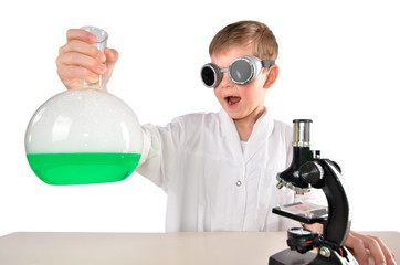 Surprised scientist boy in black glasses holds a flask in his hand