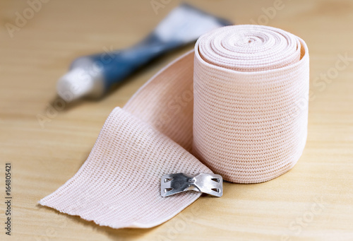 Medical elastic bandage on wood table. Canvas Print