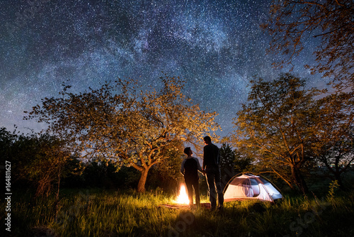 Fototapeta Rear view of romantic couple tourists standing at a campfire, holding hands near tent under trees and beautiful night sky full of stars and milky way. Night camping. Long exprose obraz na płótnie