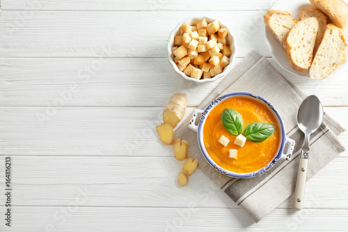Fotografía  Composition with delicious carrot soup, croutons and fresh ginger on wooden tabl