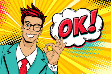 Wow pop art male face. Young handsome man in glasses smiles, winks and shows okay sign and OK! speech bubble. Vector illustration in retro comic style. Vector pop art background. Invitation poster.