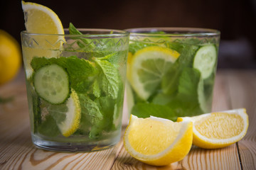 Panel Szklany Do herbaciarni Detox water, fresh organic lemonade with ice, cucumber, lemon and mint on wooden background