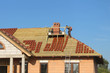 Workers laying tiles on a detached house roof