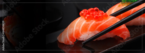 Japanese cuisine. Salmon sushi nigiri in chopsticks over black background.