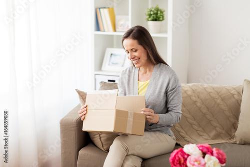 Fotografie, Obraz  smiling woman opening cardboard box