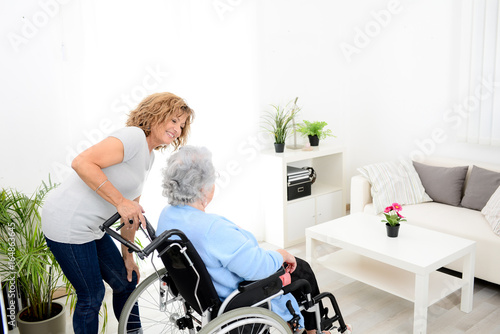 Fényképezés cheerful mature woman visiting retirement home residence with elderly senior wom