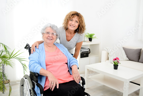 Foto  cheerful mature woman visiting retirement home residence with elderly senior wom