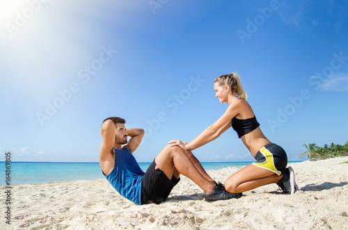 Foto  Weiblicher persönlicher Trainer, der bei der ABS-Krise am Strand hilft