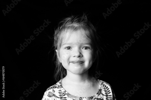 Fotomural  portrait of a little  pretty cute beautiful girl on a  dark  background
