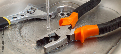 Photo plumbing tools adjustable wrench and pliers in a sink under pouring water, close