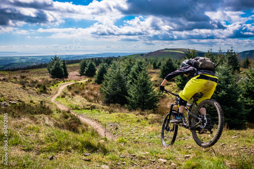 Mountain Biking in Wales - rider speeds down steep flowing trail with river Severn in the background Canvas Print