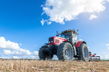 Agricultural Tractor In The Foreground With Blue Sky Background.