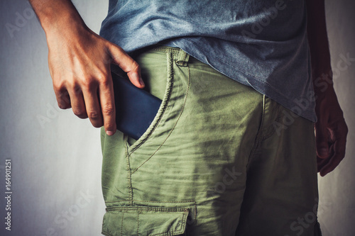 close-up of a hand about to taking a smart phone from a pant's pocket Fototapeta