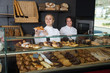 Happy woman and young girl selling pastry