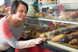 Woman choosing pastry in cafe showcase.