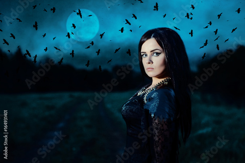 Fototapeta A young witch on background of a full moon and a flock of crows