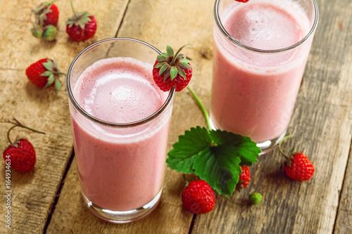 Foto op Plexiglas Milkshake Fresh strawberry milkshake on a wooden table. Healthy fruit smoothie drink. Top view, close-up shot.