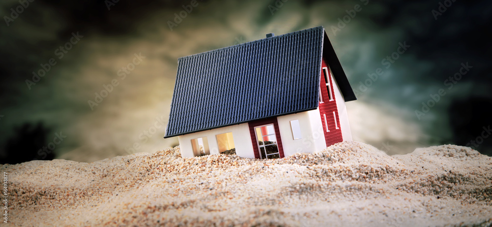 Fototapeta Miniature of house standing in sand