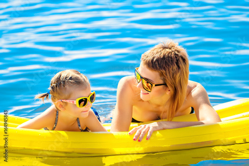 Fototapeta Mother and daughter in sunglasses floating on airbed together.