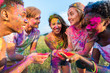 canvas print picture - cheerful young multiethnic friends holding colorful paint in hands at holi festival