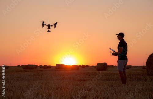 Staande foto Helicopter Man operating a professional drone at sunset