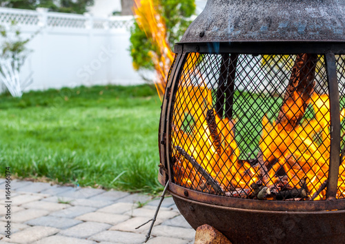Outdoor fire pit with roaring fire. Chimera in backyard with strong fire  and flames. Backyard with fire pit and white fence and lattice . - Outdoor Fire Pit With Roaring Fire. Chimera In Backyard With Strong