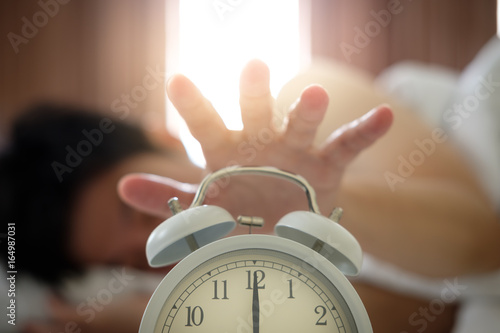 Photo The hand under the blanket extends to the alarm clock in the morning, with light orange