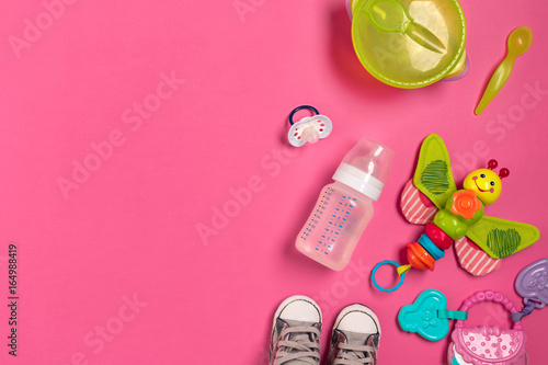 Photo Baby toys and accessories on pink background. Top view