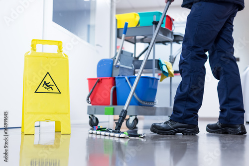 Fotografía  Worker janitor Mopping Floor In Office with trolley