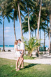Young couple embrace each other near the fresh green palm tree. They are happy. They stand on the green grass with a tropical sea and blue sky with clouds on the background.