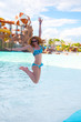 Happy woman jumping in a water park. Travel, vacation, summer holidays and happy people concept.