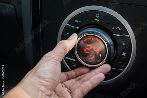 Photo Adjust air conditioner in car , Driver hand tuning temperature control in car ai