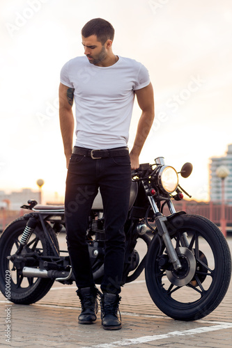 Fotomural Sporty biker handsome rider man in white blank t-shirt walk away from classic style cafe racer motorbike at sunset