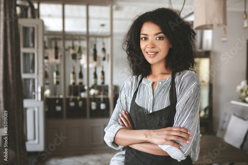 Valokuva  Portrait of beautiful African American girl wearing shirt and apron in restaurant