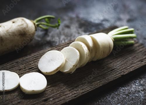 Closeup of cut daikon radish on wooden cutboard