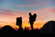 Silhouettes of a couple of hikers with backpacks standing on top of a rock enjoying dusky landscape copyspace love romance dating travelling sky dramatic colorful sunset active lifestyle.
