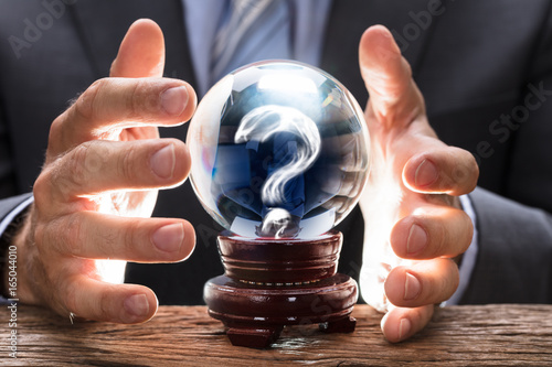Businessman Covering Crystal Ball With Question Mark Fototapeta