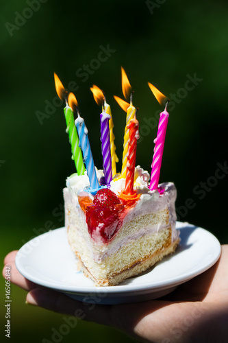 Girl Holding Beautiful Appetizing Birthday Cake With Many Candles On Green Nature Background Closeup