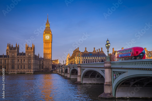 Poster London London, England - The iconic Big Ben with Houses of Parliament and traditional red double decker bus on Westminster Bridge at sunrise with clear blue sky